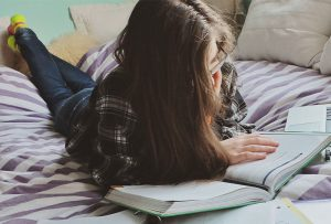 Teen girl studies a book on her bed.