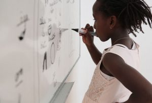 School age girl works on a white board